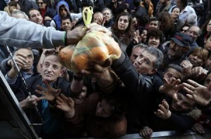 People reach out to take fruits and vegetables distributed for free by farmers during a protest against high production costs outside the Agriculture Ministry in Athens