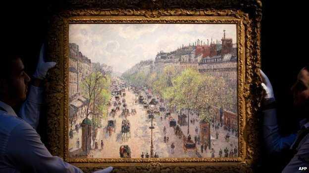 Sothebys-employees-hold-up-Camille-Pissarros-Le-Boulevard-Montmartre-matinee-de-printemps-1897