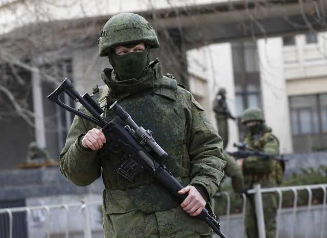 Armed men patrol around the regional parliament building in the Crimean city of Simferopol