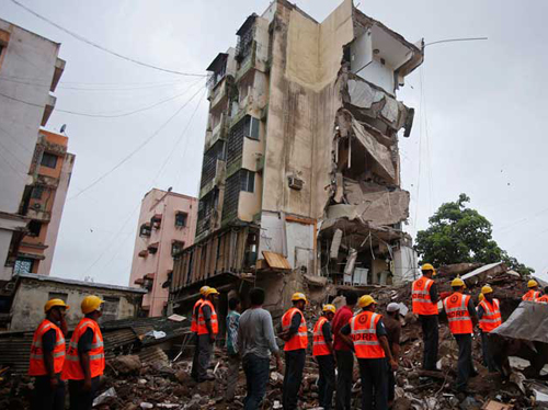 Rescue workers search through rubble at the site of a collapsed residential building in Mumbai