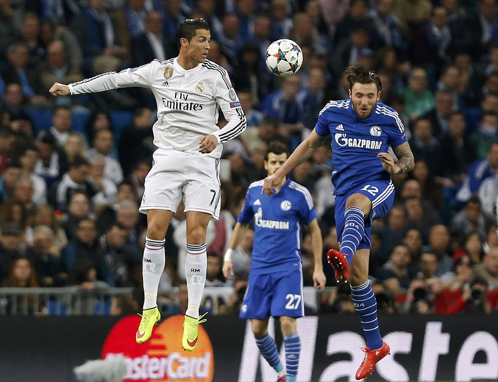 Real Madrid's Cristiano Ronaldo is challenged by Schalke 04's Marco Hoger during their round of 16 second leg soccer match in Madrid
