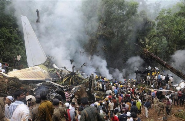 Onlookers and firefighters stand at the site of a crashed Air India Express passenger plane in Mangalore