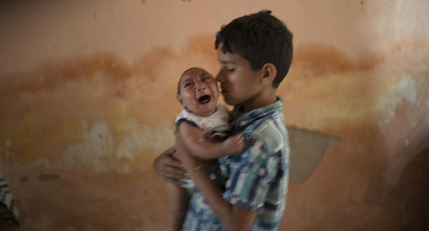 FILE - In this Dec. 23, 2015, file photo, 10-year-old Elison nurses his 2-month-old brother Jose Wesley, who was born with microcephaly, at their house in Poco Fundo, Pernambuco state, Brazil. The U.S. Centers for Disease Control and Prevention said Wednesday, Jan. 13, 2016, that it has found the strongest evidence so far of a possible link between a mosquito-borne virus and a surge of birth defects in Brazil. (AP Photo/Felipe Dana, File)