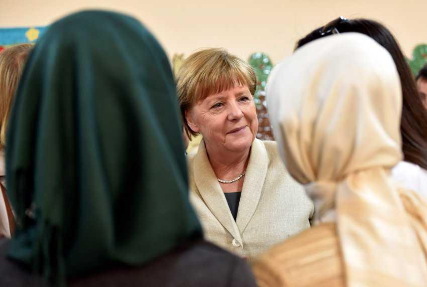 """HANDOUT- Bundeskanzlerin Angela Merkel (CDU, M) unterhält sich am 23.04.2016 in der Kindergartengruppe des Flüchtlingslagers Nizip I mit Kindergärtnerinnen. Merkel informierte sich bei ihrer Reise gemeinsam mit EU-Ratspräsident Tusk und dem Vizepräsidenten der Europäischen Kommission, Timmermans über die Umsetzung der EU-Türkei-Flüchtlingsvereinbarung. Foto: Bundesregierung/Steffen Kugler/dpa (ACHTUNG: Nur zur redaktionellen Verwendung im Zusammenhang mit der aktuellen Berichterstattung und nur bei Nennung: """"Foto: Bundesregierung/Steffen Kugler/dpa"""") +++(c) dpa - Bildfunk+++"""